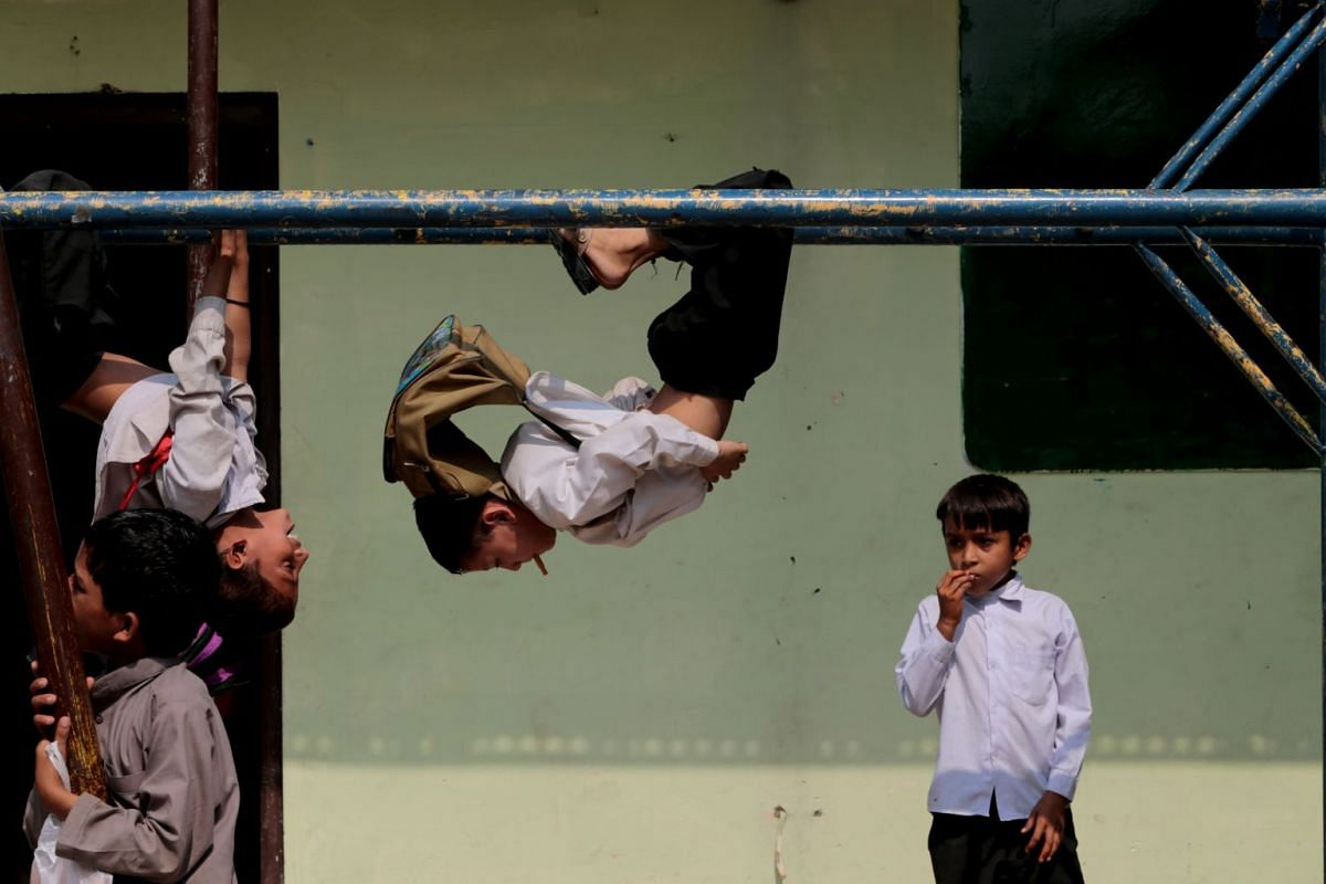 Children play on the monkey bars at the Mashal Model school in Islamabad, Pakistan.