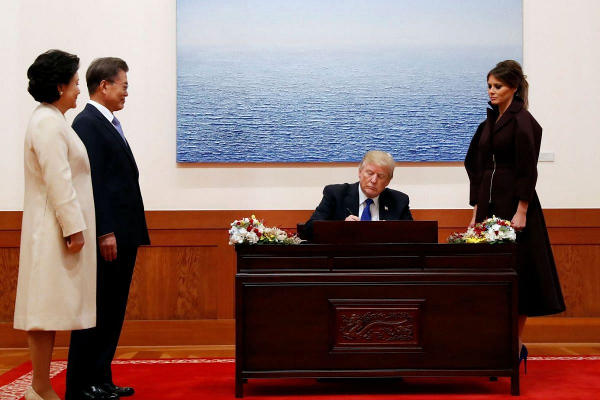 US President Donald Trump signs the guest book as US First Lady Melania, South Korea's President Moon Jae In and South Korea's First Lady Kim Jung Sook look on at the presidential Blue House in Seoul on Nov 7, 2017.