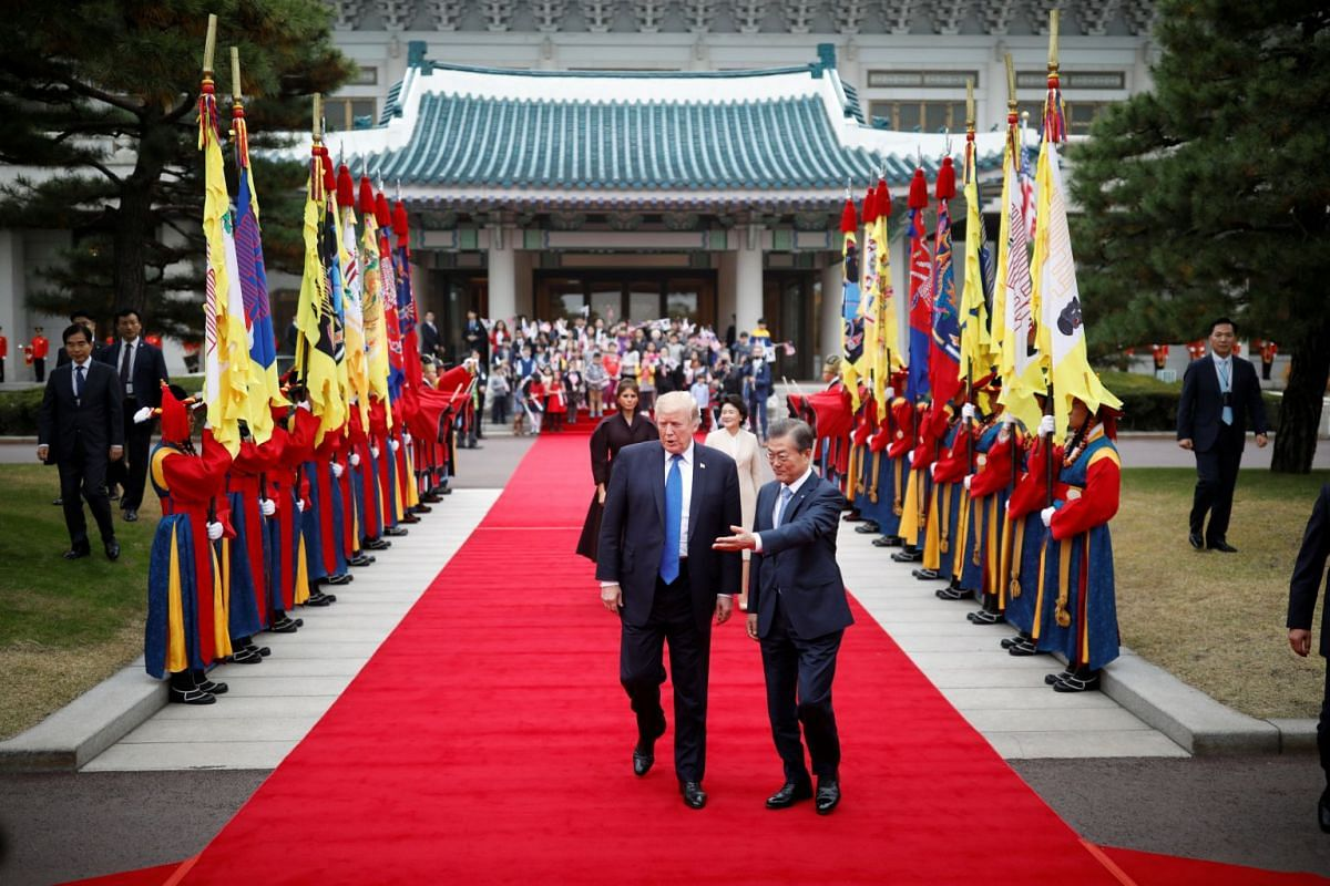 US President Donald Trump walks with South Korea's President Moon Jae In during a welcoming ceremony at the presidential Blue House in Seoul on Nov 7, 2017.