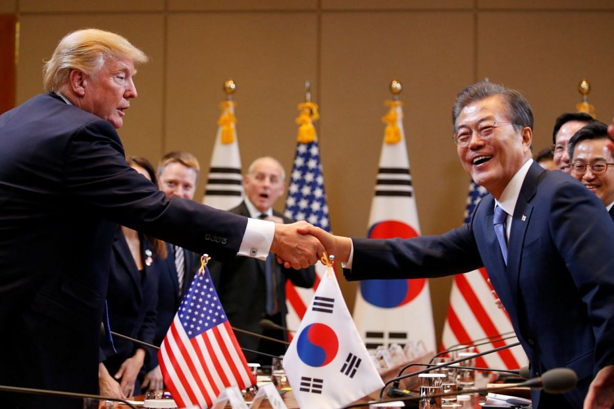 US President Donald Trump and South Korea's President Moon Jae In shake hands during a meeting at the presidential Blue House in Seoul on Nov 7, 2017.