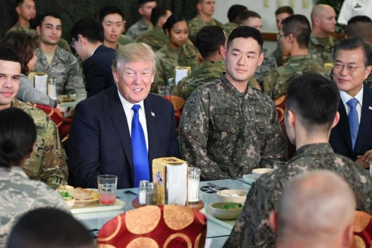 US President Donald Trump talks to military personnel while South Korean President Moon Jae In looks on at Camp Humphreys in Pyeongtaek, south of Seoul on Nov 7, 2017.
