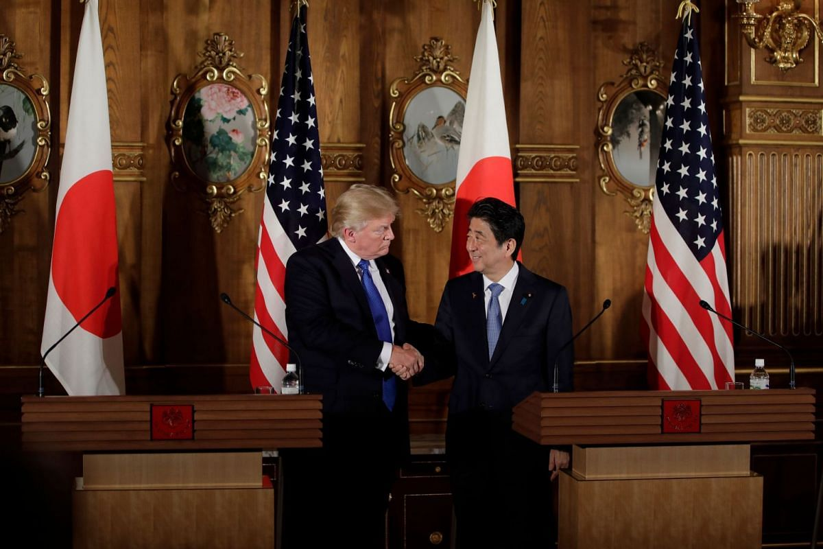 US President Trump shakes hands with Japan's PM Abe (right) during the news conference.