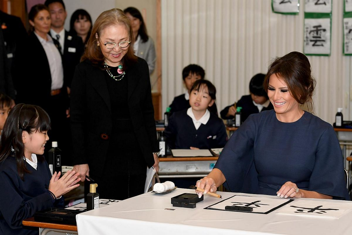 US First Lady Melania Trump (right) writes calligraphy with the help of a school girl.