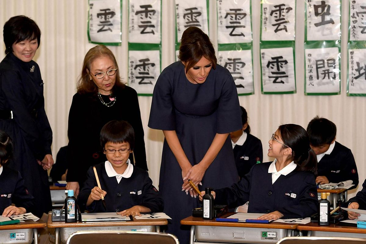 US First Lady Melania Trump (centre) speaks to a student while attending a calligraphy class of 4th graders with Mrs Akie Abe (left).