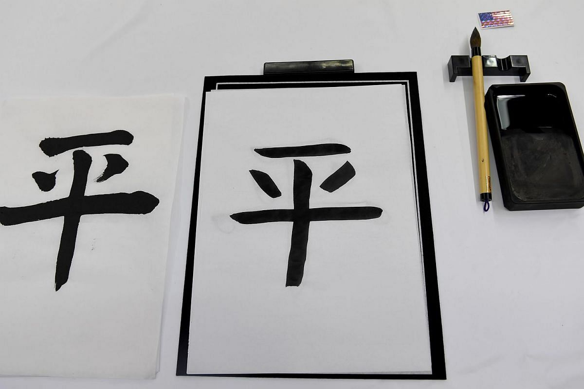 """A caligraphy (centre) written by US First Lady Melania Trump is seen while attending a calligraphy class. Mrs Trump and Mrs Abe wrote Chinese characters together meaning """"Peace""""."""