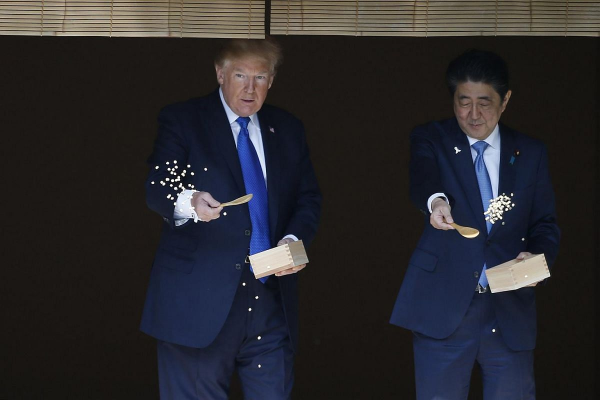US President Donald Trump (left) and Japanese Prime Minister Shinzo Abe (right) feed koi fish during a welcoming ceremony.