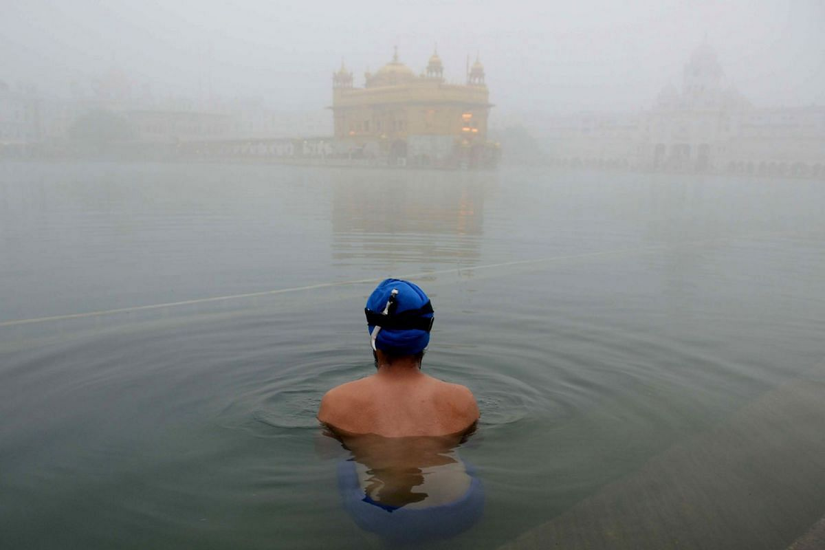 An Indian Sikh devotee takes a dip in the holy sarovar (water tank) on a foggy day at the Golden Temple in Amritsar on November 7, 2017.