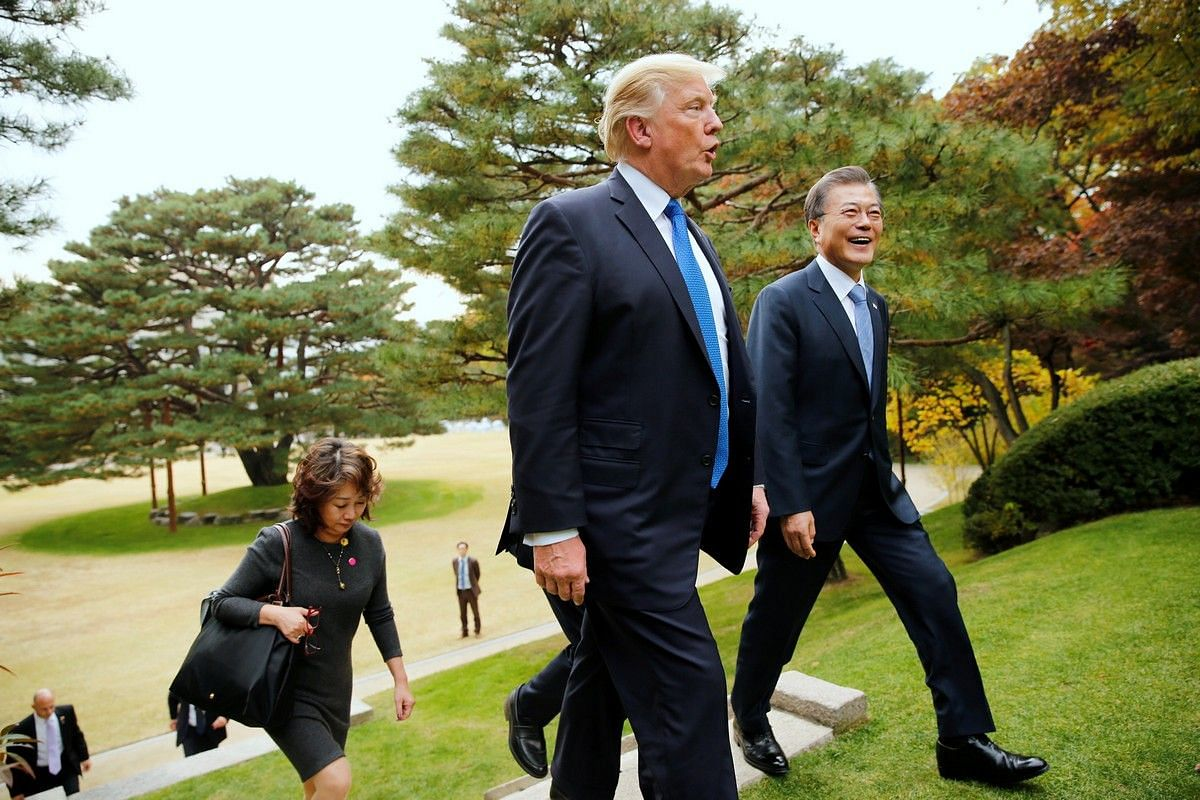 US President Donald Trump and South Korea's President Moon Jae In walk on the grounds of the presidential Blue House in Seoul on Nov 7, 2017.