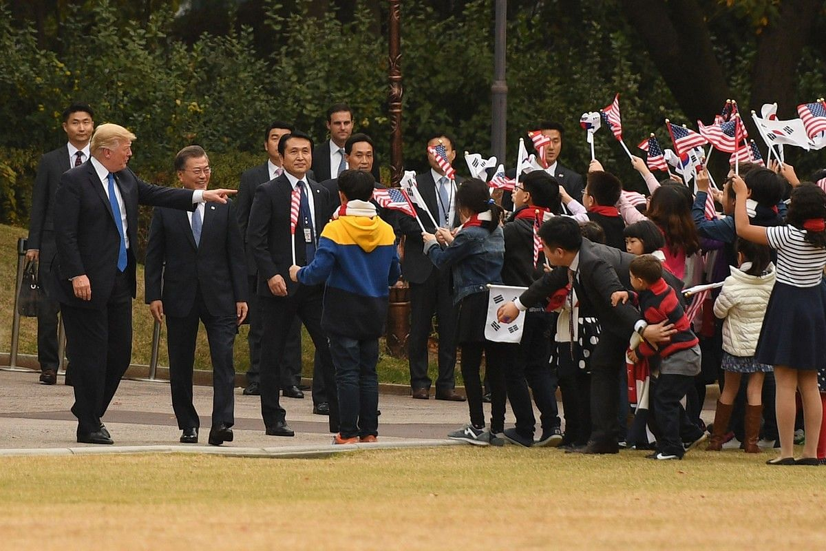 US President Donald Trump and South Korea's President Moon Jae In walk past children holding US and South Korea flags on the grounds of the presidential Blue House in Seoul on Nov 7, 2017.