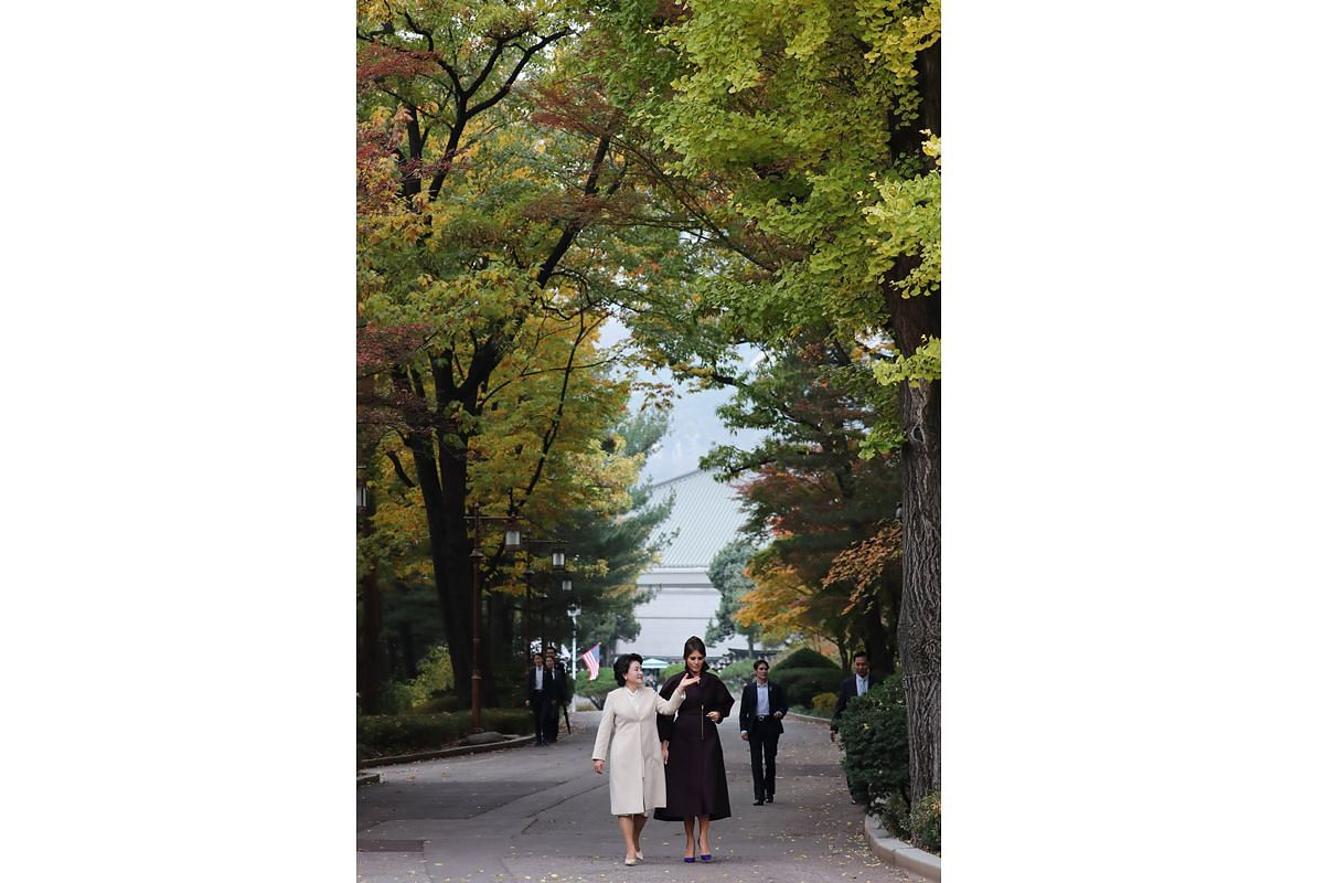South Korean First Lady Kim Jung Sook and US First Lady Melania Trump walk through the Nokjiwon garden on the grounds of the presidential Blue House in Seoul on Nov 7, 2017.