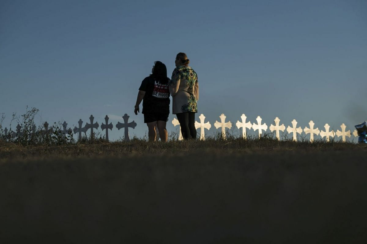 Sonia Yanez, left, from New Braunfels, and Laura Torres, from San Antonio, look upon a long row of 26 crosses set up on the edge of Sutherland Springs, Texas, Nov. 6, 2017, one for each person killed by a single gunman as they attended a service on S