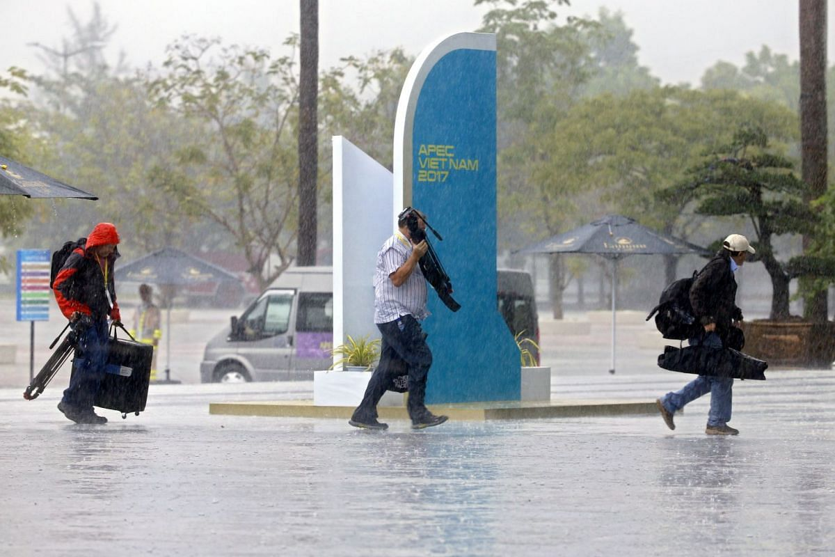 Members of the media run under the rain at the International Media Center (IMC) in Da Nang, Vietnam, November 8, 2017. The APEC Vietnam 2017 summit brings together world leaders from 21 member nations. It is Vietnam's second time hosting the APEC sum