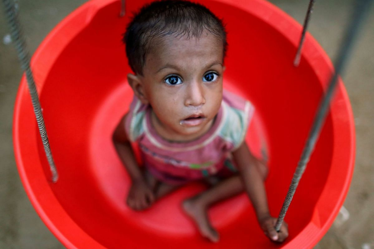 A Rohingya refugee girl is weighed at the emergency nutrition treatment center in Balukhali refugee camp near Cox's Bazar, Bangladesh November 8, 2017.