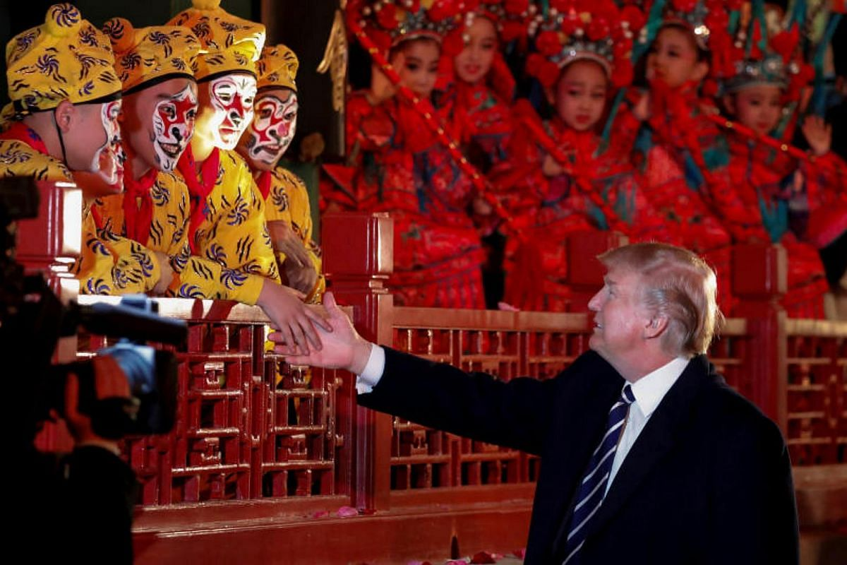 US President Donald Trump shakes hands with opera performers at the Forbidden City in Beijing, China on Nov 8, 2017.