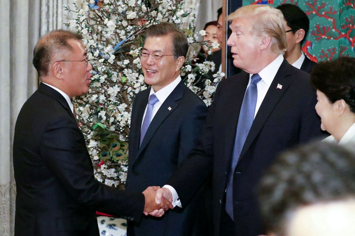 US President Donald Trump shakes hands with shakes hands with Chung Eui Son, Hyundai Motor Co's vice-chairman and son of the Hyundai Motor Group chairman, during a state dinner at the presidential Blue House in Seoul on Nov 7, 2017.