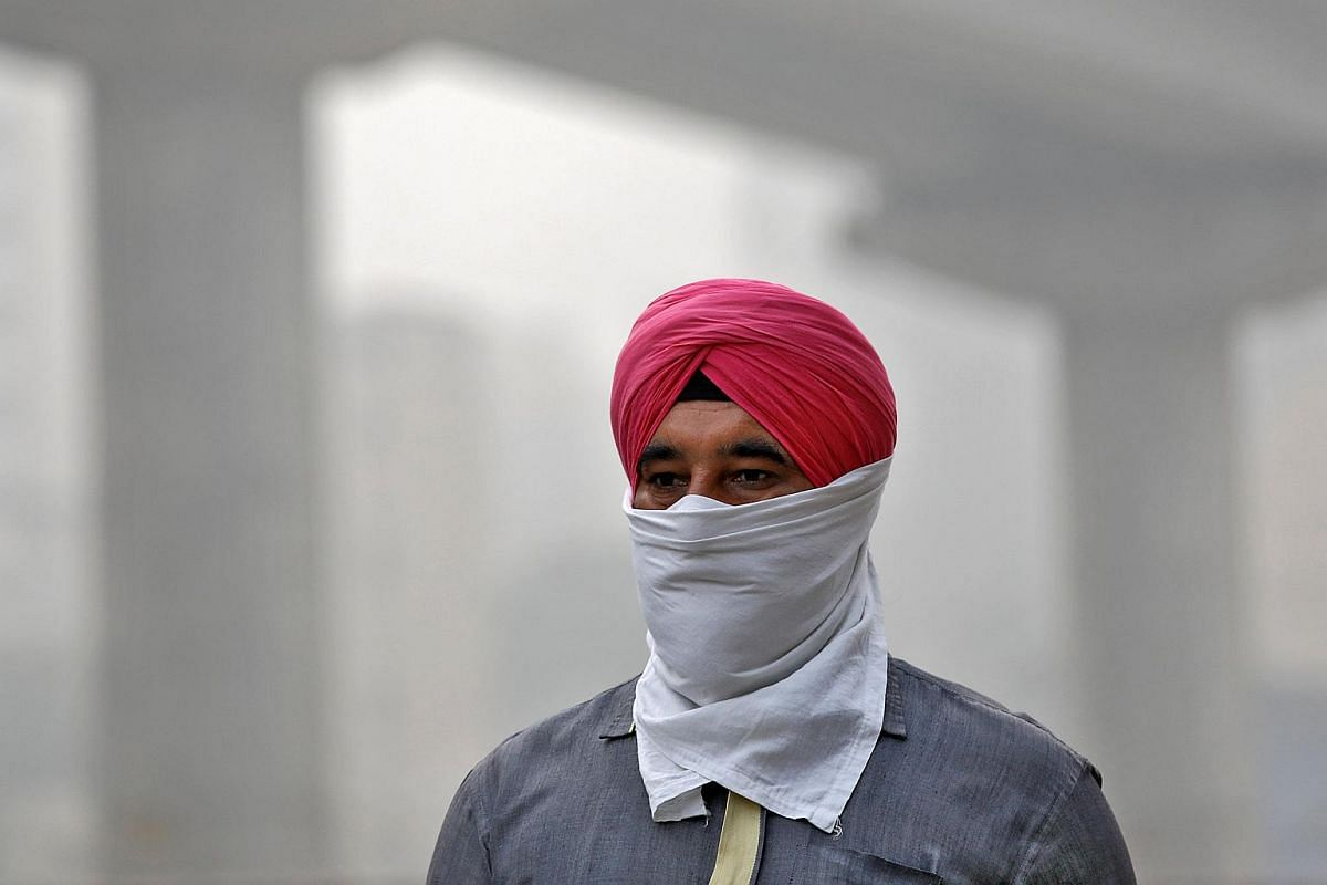 A man covers his face as he walks to work, in New Delhi.