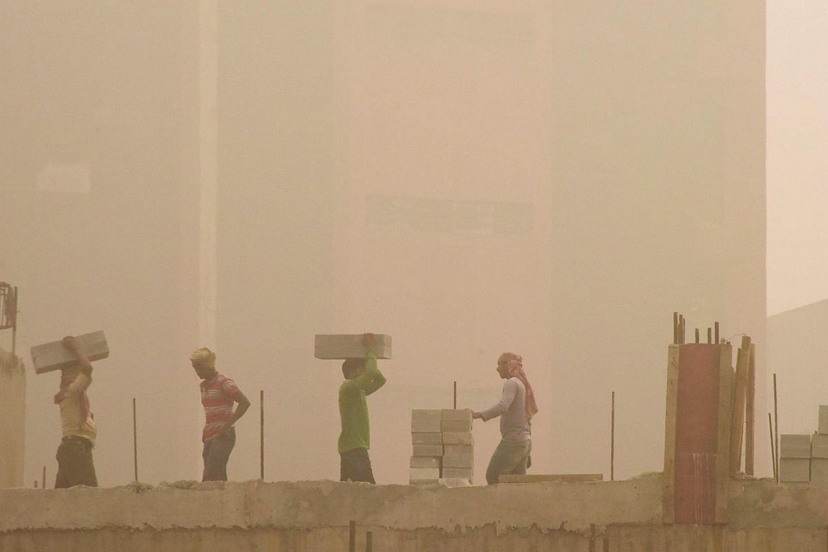 Indian labourers work on a construction site during heavy smog conditions in New Delhi.