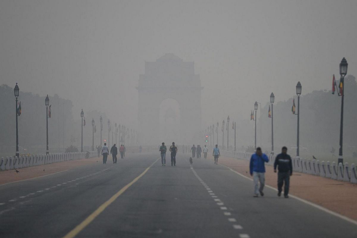 People walk early in the morning as smog covers India Gate war memorial in New Delhi.