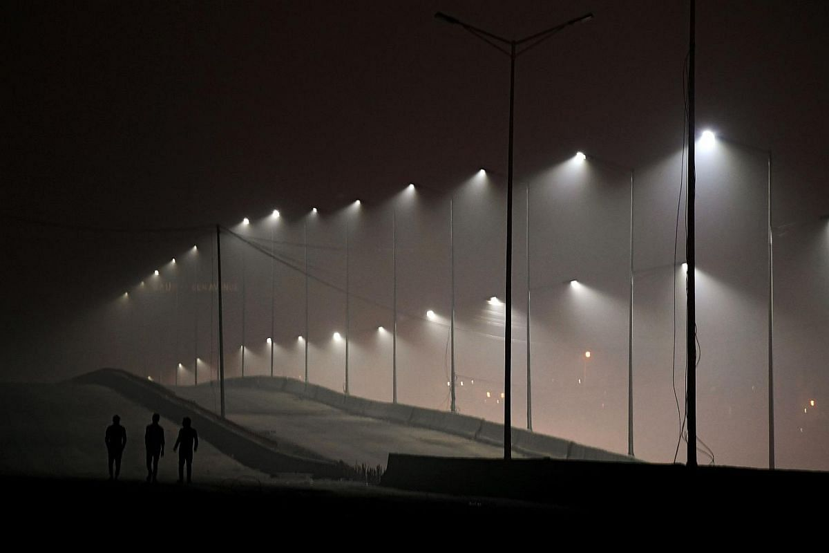 People walking on an under-construction flyover as smog covers the capital's skyline in New Delhi.