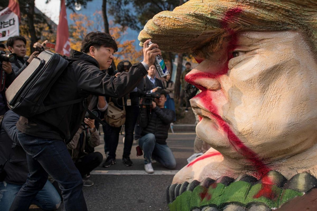 "A anti-Trump protester spray defaces a statue depicting US President Donald Trump during a rally outside the National Assembly in Seoul on November 8, 2017. US President Donald Trump offered North Korean leader Kim Jong-Un what he called ""a path towa"