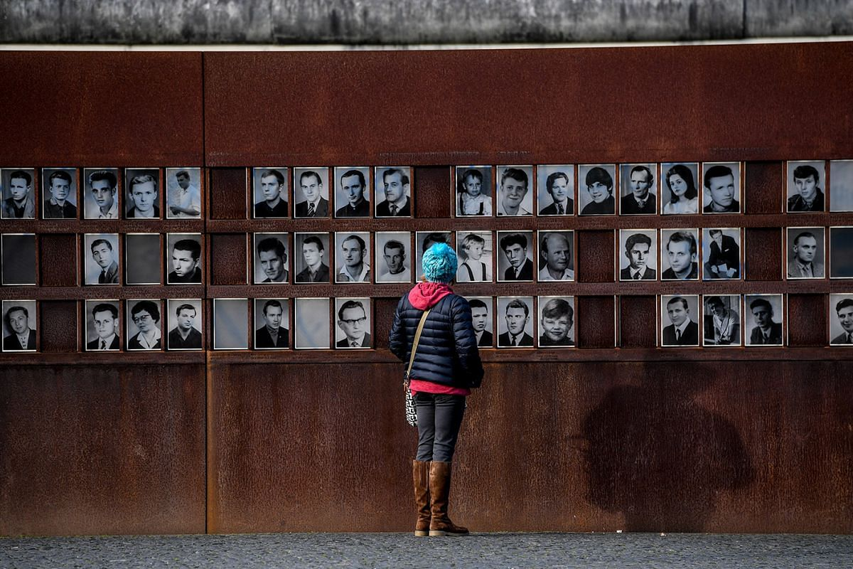 A woman looks at portraits of people who were killed or died at the Berlin Wall connected to the GDR border regime, at the Berlin Wall memorial site in Berlin, Germany, November 8,  2017. November 9 marks a significant date in German history when bot
