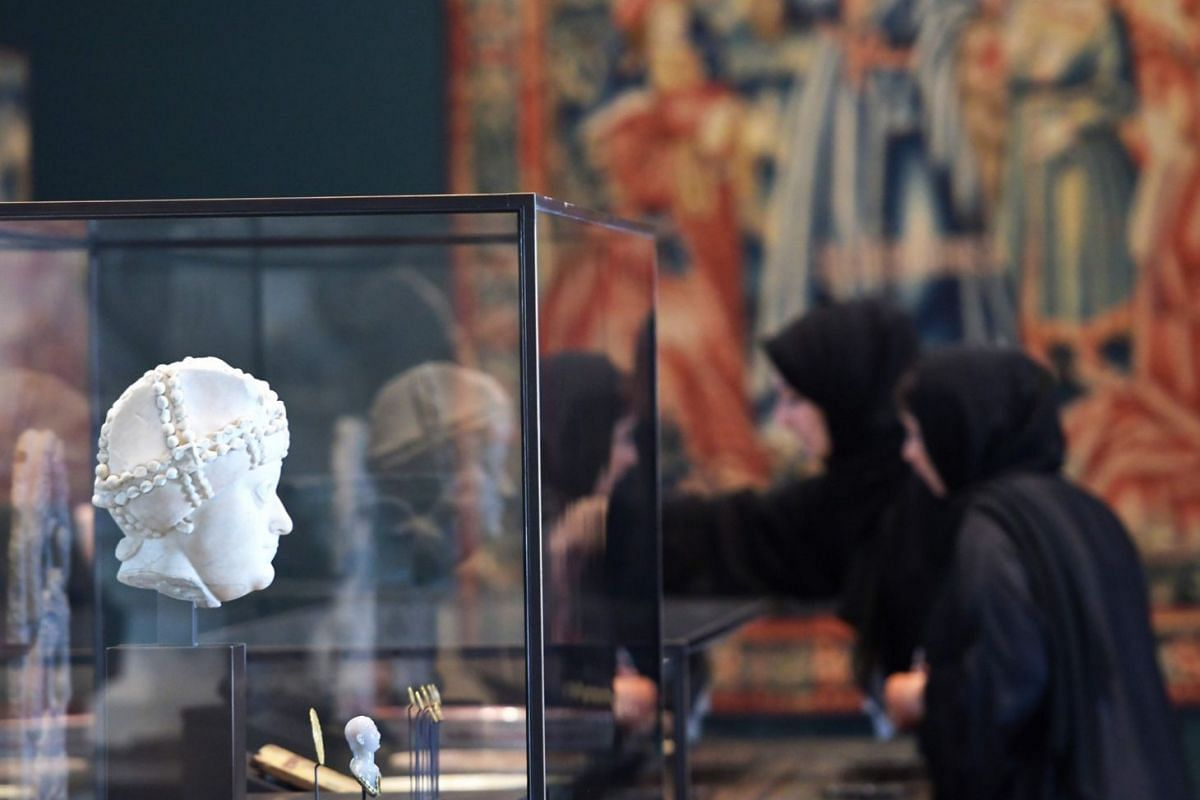 Women look at statues on display in a gallery at the Louvre Abu Dhabi Museum on Nov 6, 2017.