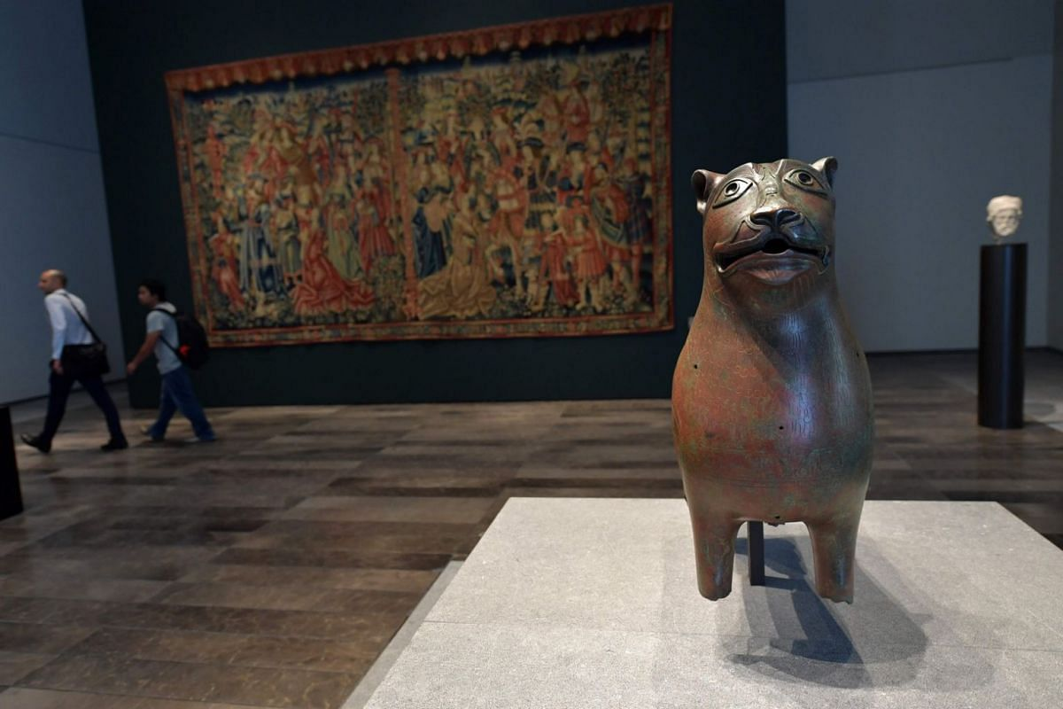 An ancient bronze statue titled Lion de Mari-cha is seen on display at the Louvre Abu Dhabi Museum.