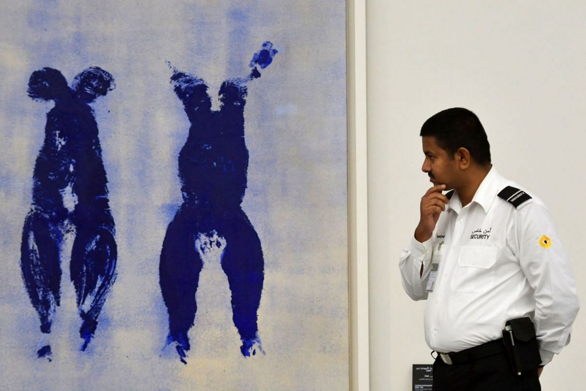 A security guard looks at Untitled Anthropometry Ant 110 by artist Yves Klein on display at the Louvre Abu Dhabi Museum.