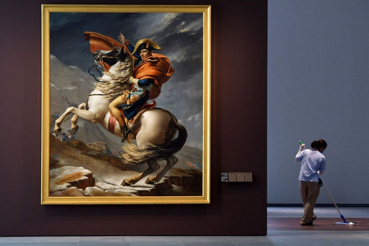 A cleaner mops the floor next to the painting titled Napoleon Bonaparte, First Consul, Crossing the Alps by French artist Jacques-Louis David at the Louvre Abu Dhabi Museum.