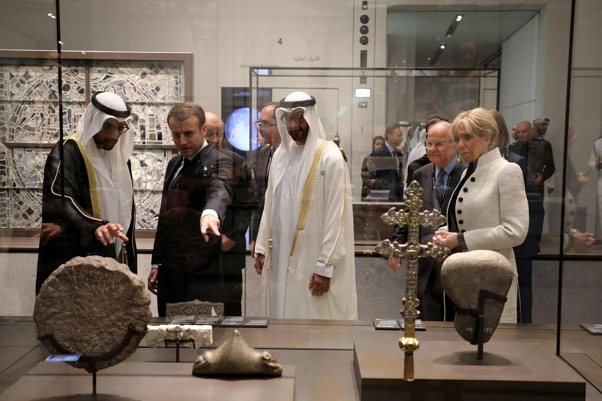 French President Emmanuel Macron (second left) and his wife Brigitte Macron (right) look at a piece of art as they visit the Louvre Abu Dhabi Museum on Nov 8, 2017 during its inauguration.