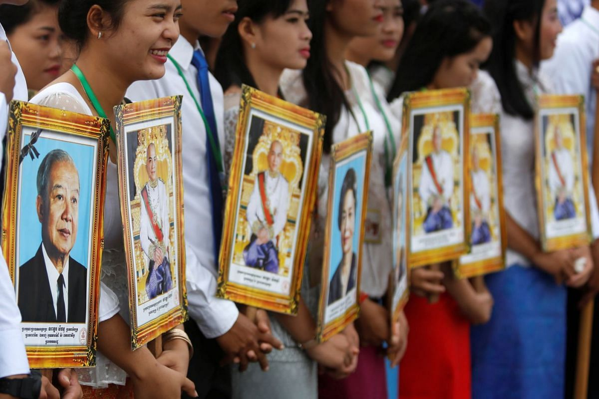 People hold portraits of late king Norodom Sihanouk and King Norodom Sihamoni and queen mother Monineath Sihanouk while attending the celebration marking the 64th anniversary of the country's independence from France, in Phnom Penh, Cambodia November