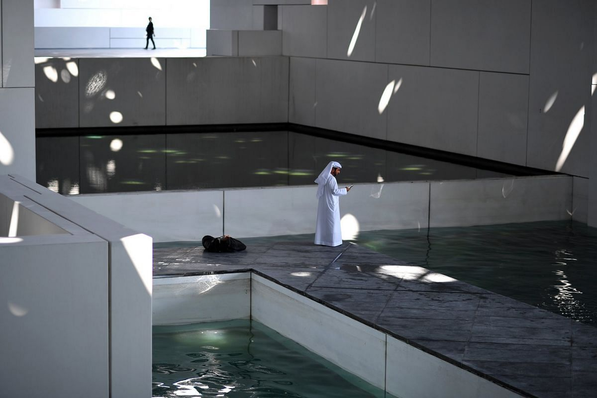 A man dressed in a white thobe stands in an area providing a boat access to the Louvre Abu Dhabi as sunlight bursts through a randomly perforated double dome at the museum's pre-opening event on Nov 7, 2017.