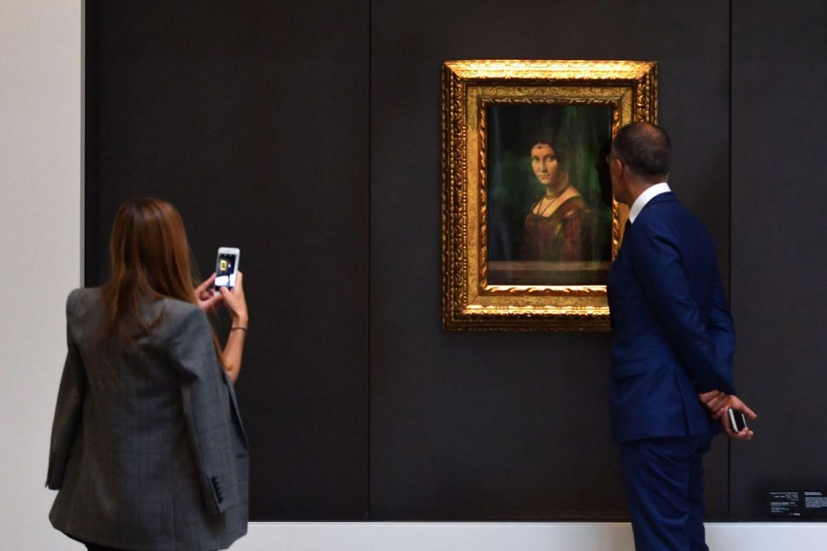 A couple looks at a painting titled La Belle Ferroniere by Leonardo Da Vinci inside a gallery at the Louvre Abu Dhabi. The museum currently has some 300 pieces on loan, including an 1887 self-portrait by Vincent van Gogh.