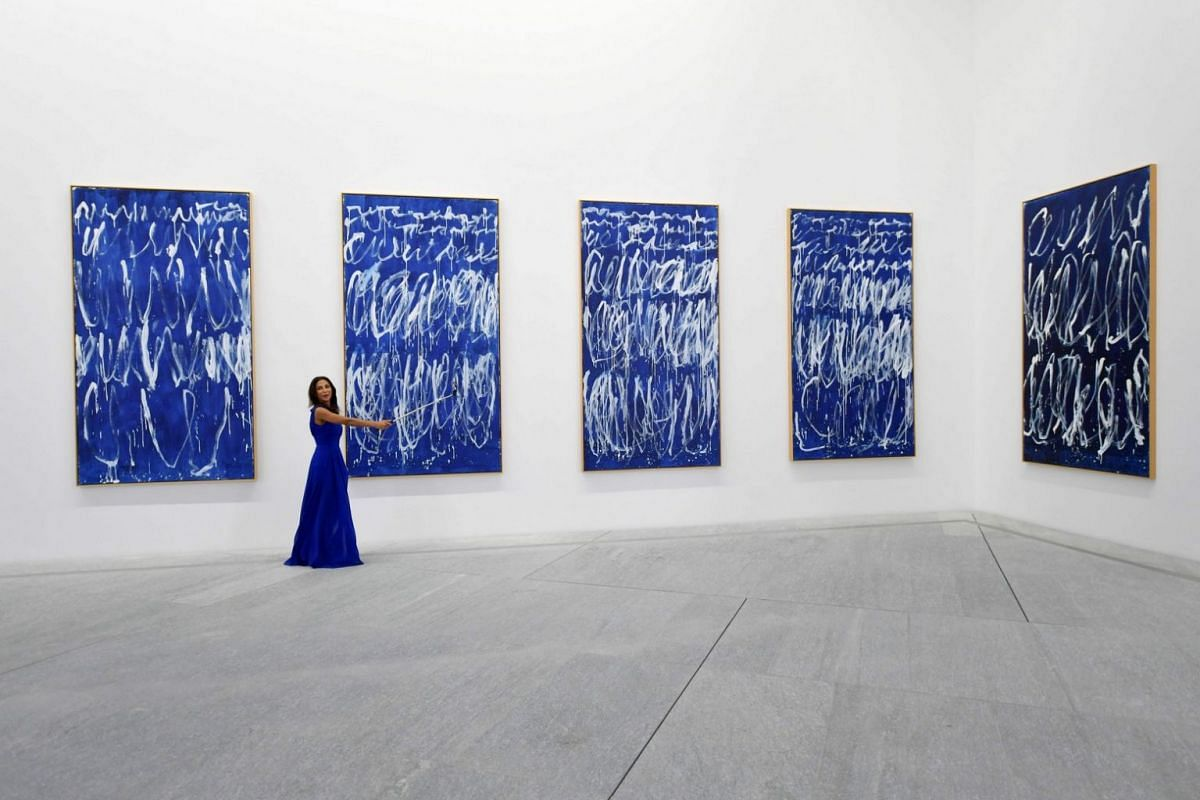 A woman takes a selfie in front of part of a series of nine panels titled Untitled I-IX by American painter Cy Twembly at the Louvre Abu Dhabi Museum on Nov 6, 2017.