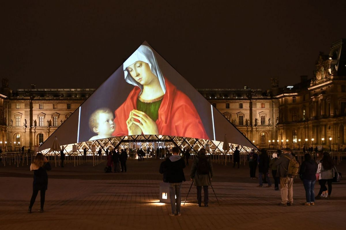 Images are projected onto the Louvre Pyramid in Paris at night on November 8, 2017 to mark the opening of the Louvre Abu Dhabi Museum on Saadiyat island in the Emirati capital. More than a decade in the making, the Louvre Abu Dhabi opened its doors o