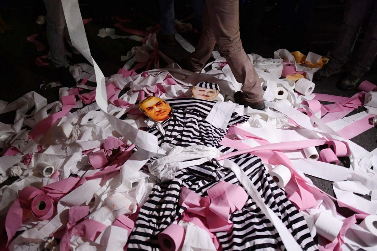 People walk over toilet paper thrown over the portraits of the ruling coalition's leaders Liviu Dragnea (PSD) and Calin Popescu Tariceanu (ALDE) as they take part in a demonstration on November 8, 2017, in the front of the Government headquarters, in