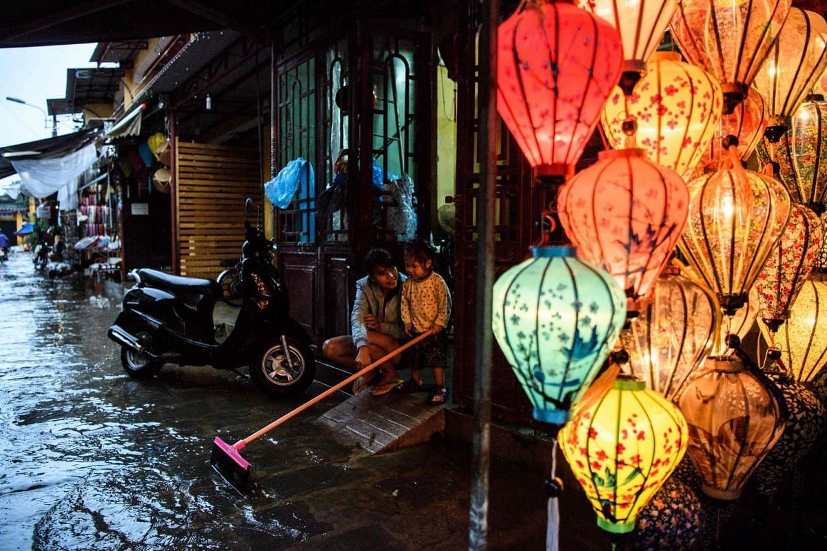 A mother and her child sit in their house entrance next to a lantern shop in the town of Hoi An on November 8, 2017 following days of heavy rains after Typhoon Damrey hit the coast.