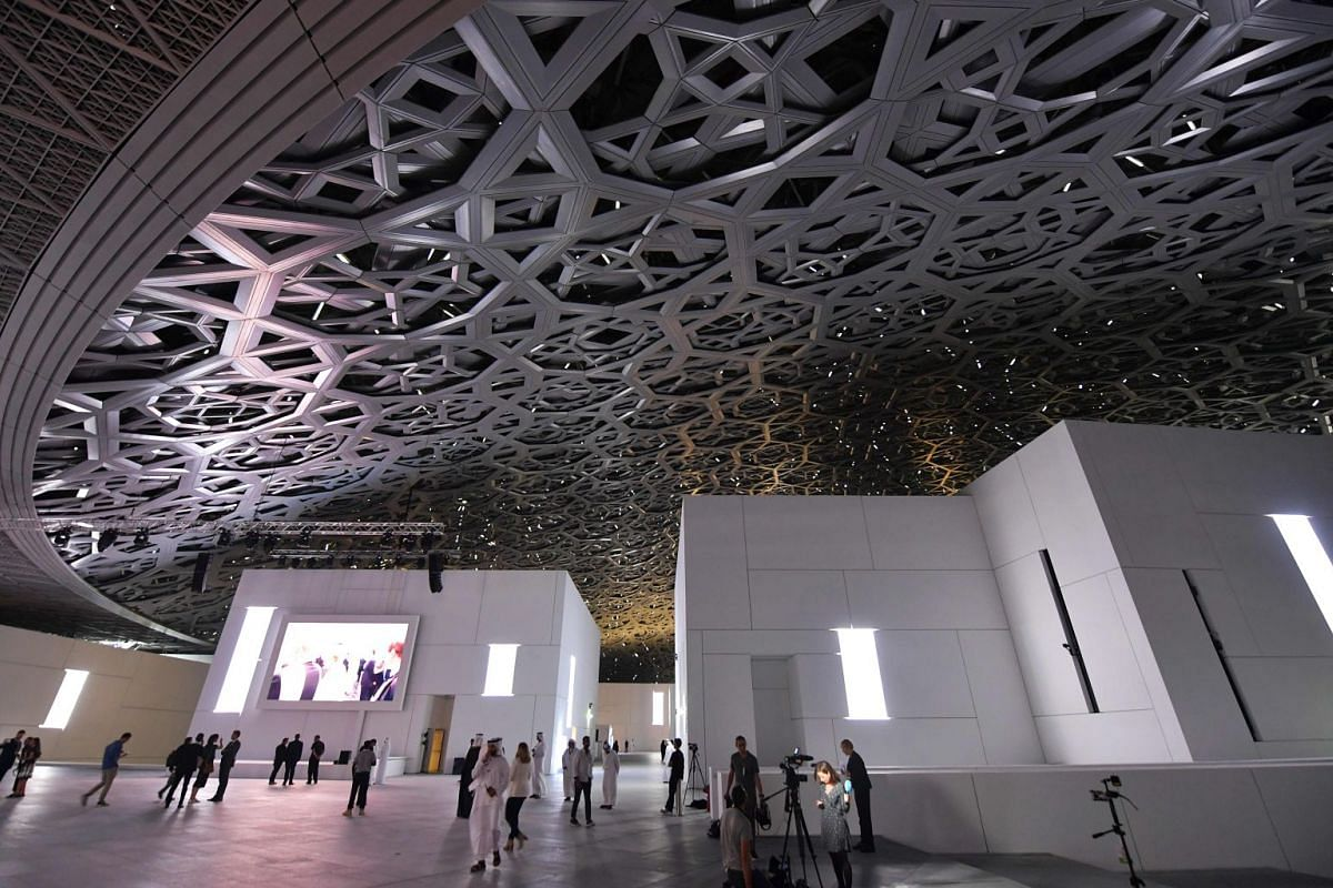 A general view shows people walking under the dome at the Louvre Abu Dhabi Museum that was designed by French architect Jean Nouvel during its inauguration on November 8, 2017 on Saadiyat island in the Emirati capital. More than a decade in the maki