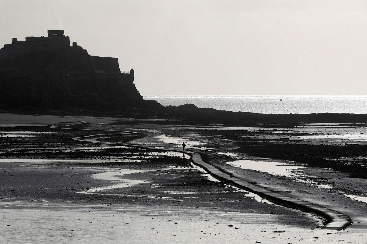 A man walks out on the tidal causeway to Elizabeth Castle in St Helier, Jersey, Britain, November 9, 2017
