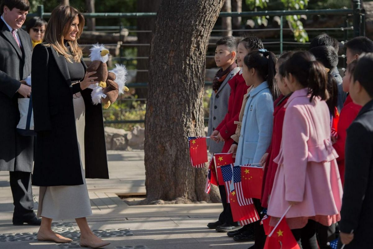 US First Lady Melania Trump (second left) offers stuffed toy eagles, from the US, to children at the Beijing Zoo in Beijing, China on Nov 10, 2017.