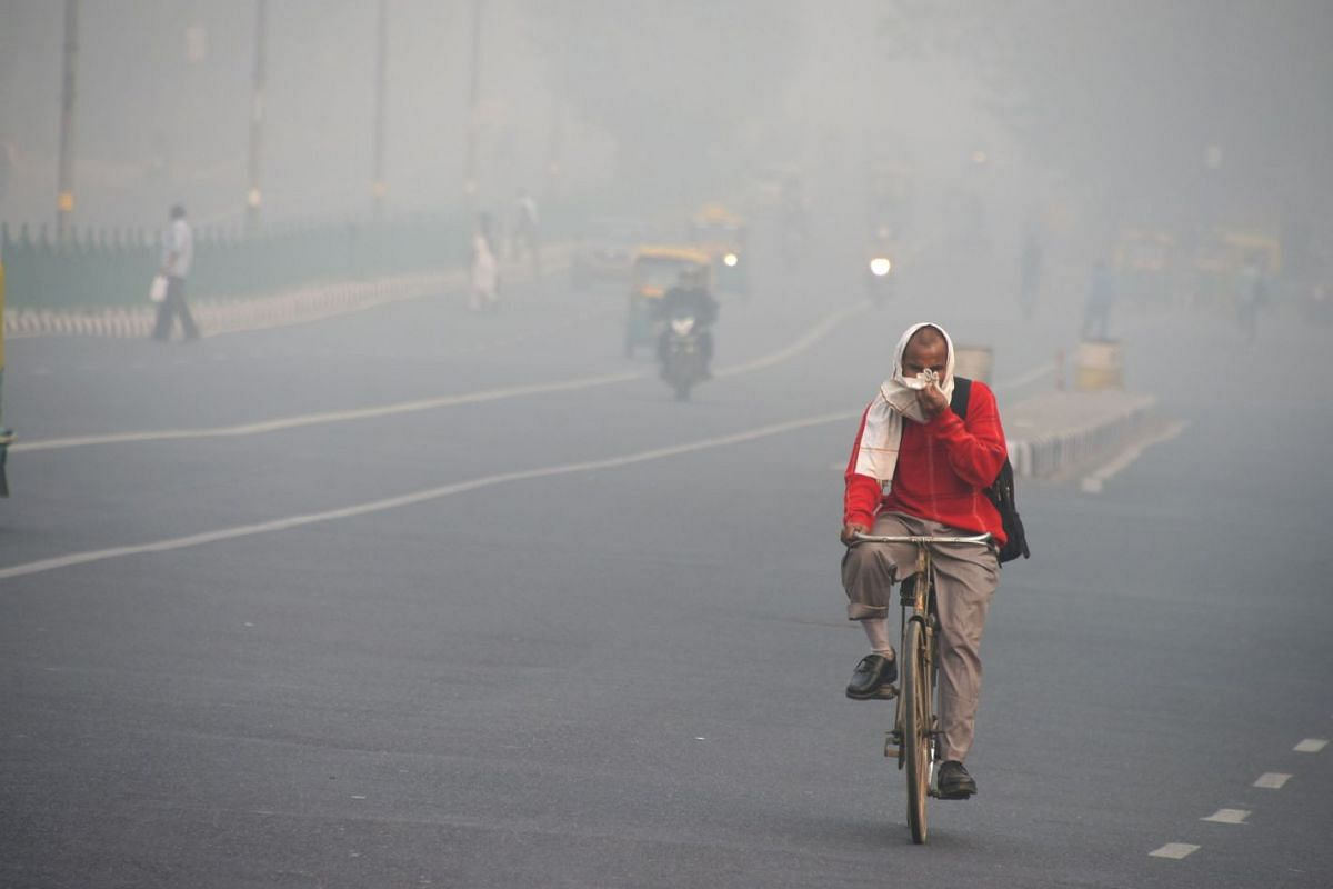 An Indian man rides a bike amid heavy smog on a street of New Delhi on November 10, 2017. Large swathes of India's northern states remained under dense smog that has shut hundreds of thousands schools, disrupted air and railway services and forced re