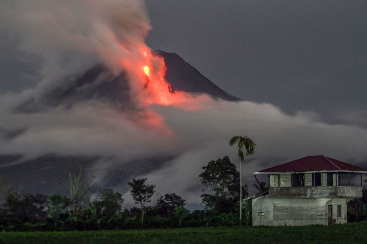 This slow-shutter speed photograph shows the eruption of Mount Sinabung volcano as seen from Simpang Ampat village, in Karo, North Sumatra, on November 10, 2017. Sinabung roared back to life in 2010 for the first time in 400 years, after another peri