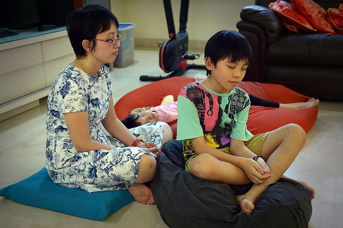 Dr Koh Li Wearn practising meditation at home with her children, Jon Yew and Jean Anne. Ms Lim Yu Lin doing a mindfulness breathing exercise with her children, Isabel and Leon.