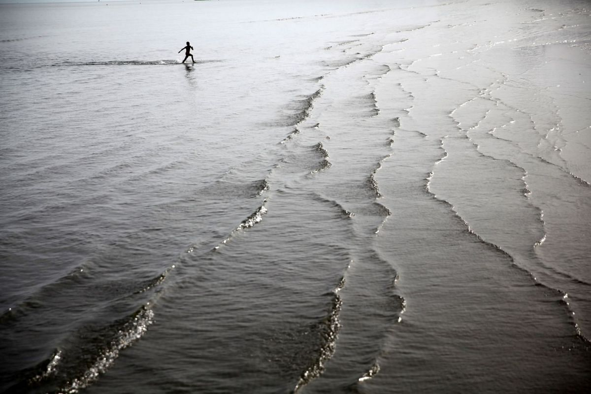 A boy runs in shallow water on a beach in the coastal city of Larnaca, Cyprus November 12, 2017.