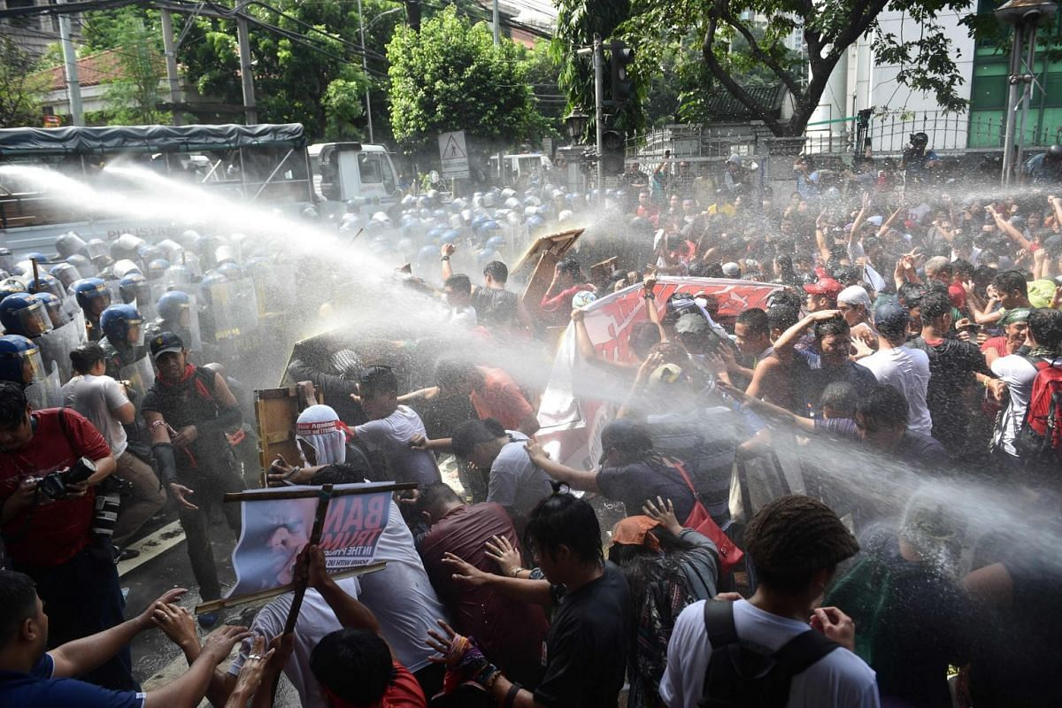 Riot policemen use water cannon on protesters trying yo march to the ASEAN Summit venue during the 31st Association of South East Asian Nations (ASEAN) Summit in Manila on November 13, 2017.
