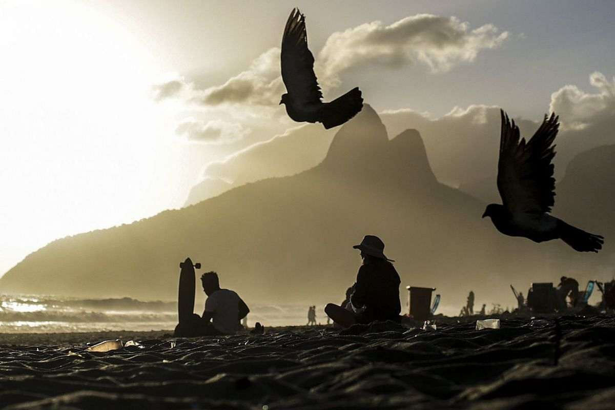 Pigeons fly during the sunset on the beach of Ipanema in Rio de Janeiro, Brazil, 13 November 2017.