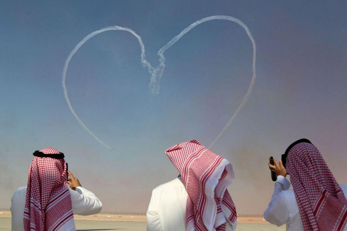 Visitors take pictures as Al Fursan aerobatic team of the United Arab Emirates Air Force performs during the Dubai Airshow in Dubai, UAE November 13, 2017.
