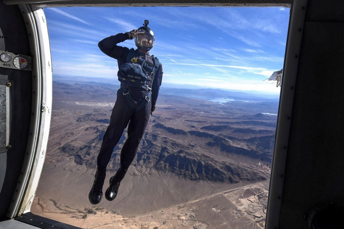 A member of the Air Force's Wings of Blue Parachute Demonstration Team salutes as he jumps out of an aircraft, during the opening ceremony of Aviation Nation 2017 Nellis Air and Space Expo at Nellis Air Force Base, Nev., November 10, 2017.