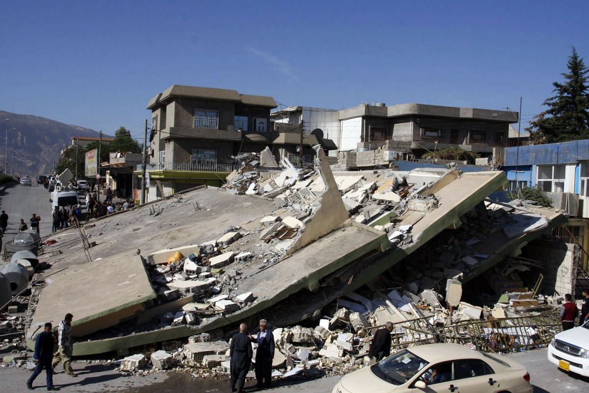 People gather around a levelled building in the mountainous town of Darbandikhan in Iraqi Kurdistan on November 13, 2017, following a 7.3-magnitude quake that hit the Iraq-Iran border area.
