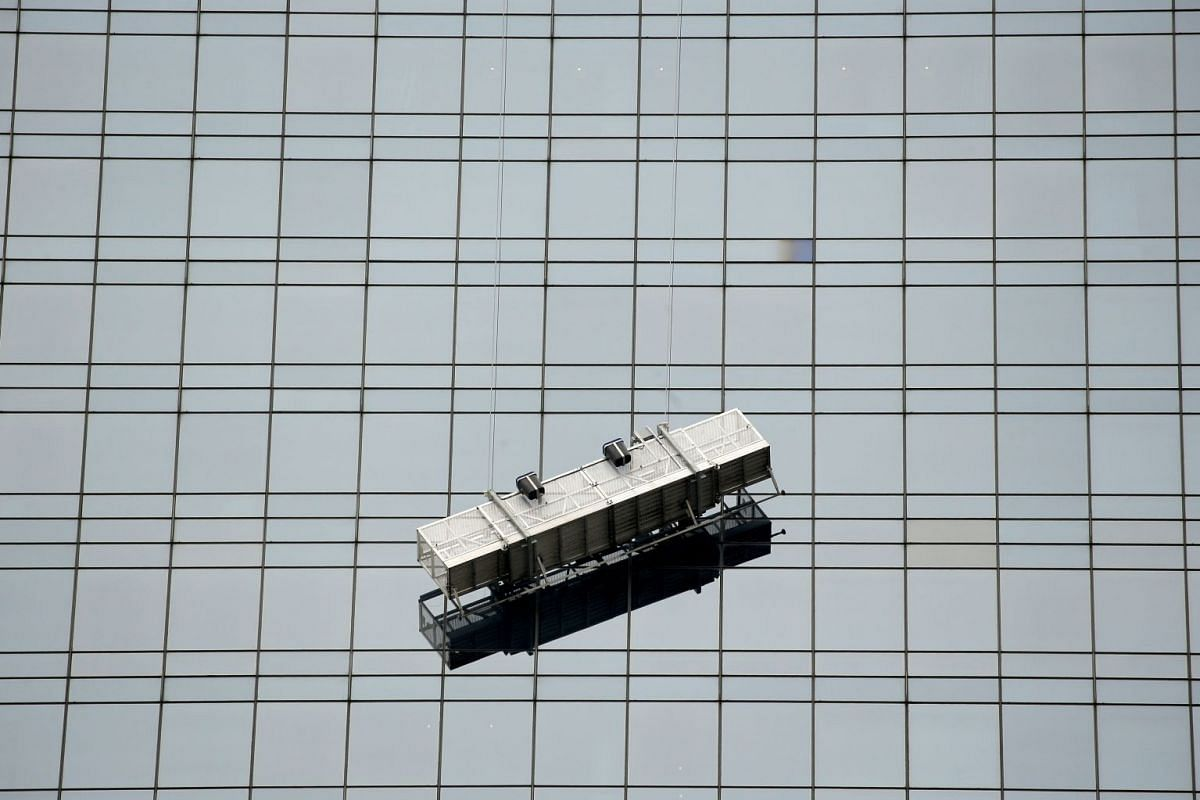 A window washing scaffolding unit hangs precariously from a skyscraper at Columbus Circle in Midtown Manhattan in New York City, U.S., November 14, 2017.